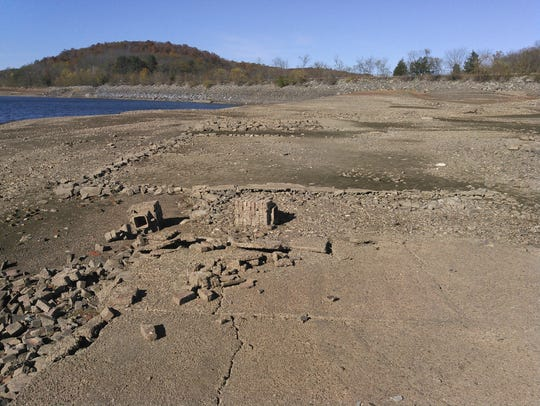 Foundations of old homes are now visible as water levels