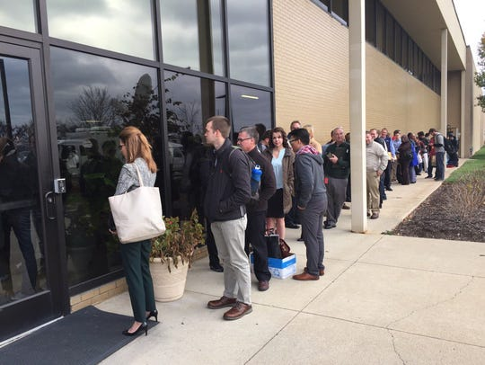Carrier employees wait to enter the building.