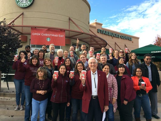 """New Mexico State University Chancellor Garrey Carruthers, center, sent this photo from his Twitter account, along with the caption: """"Aggies saluting Aggie Kevin Johnson as the new CEO of Starbucks. Way to go Kevin."""""""