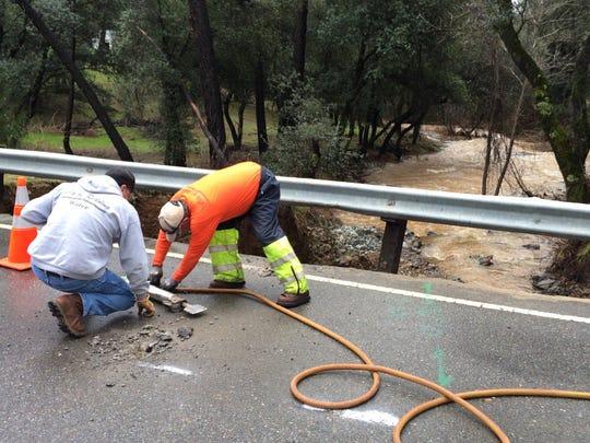 Crews start to work on a bridge and culvert damaged by heavy floods on Monday.