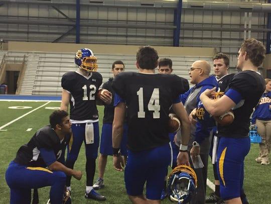 Eric Eidsness (center) talks with SDSU quarterbacks during a practice in 2017.