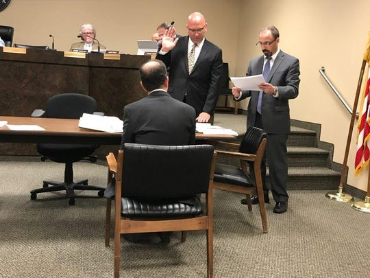 Teddy Tarabokija places his hand on the Bible as Board Secretary Lou Alfano administers the oath of office.
