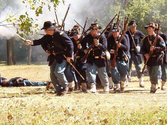 Iron Brigade reenactors move forward during a battle