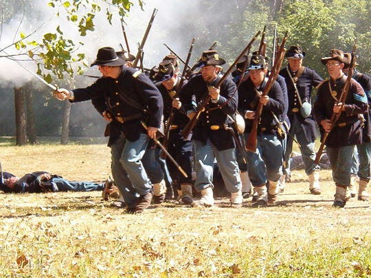 Iron Brigade reenactors move forward during a battle at the National Railroad Museum in Ashwubenon. The brigade was involved in the battle of Gettysburg from July 1-3, 1863.
