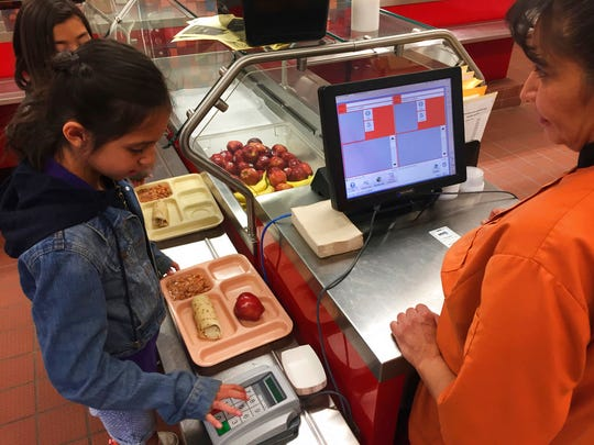 In this Thursday, May 4, 2017 photo, third grader Elliana Vigil punches in his student identification meal to pay for a meal at Gonzales Community School in Santa Fe, N.M. All students are offered the same lunch at Gonzales and other Santa Fe public schools to avoid any chance of embarrassing students whose parents may have fallen behind on meal payments. New Mexico in April became the first state to outlaw the shaming of children for any unpaid meals. (AP Photo/Morgan Lee)