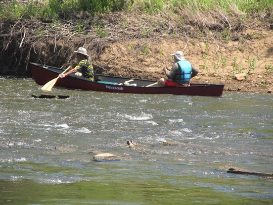 A pair of in a canoe in some fast moving water on the