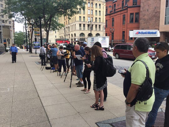 Members of the news media wait for Marcus Hutchins, a British malware expert charged with fraud in Milwaukee, to appear for court.