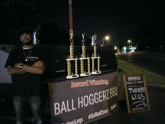 Merritt Bailey poses with trophies his barbecue company