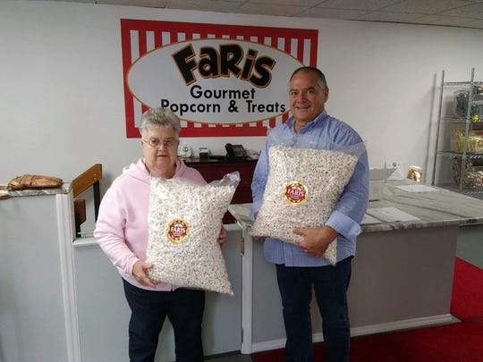 """Brown Bag Lunch Coordinator Barb Thill, left, stands with Jeff Faris, owner of Faris Gourmet Popcorn & Treats. Barb """"popped in"""" weekly to collect five large bags of popcorn; in all a total of 60 bags were donated this year."""