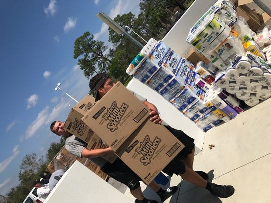 Members of the Golden Gate High School football team helped package supplies and distribute them in Immokalee to people affected by Hurricane Irma.