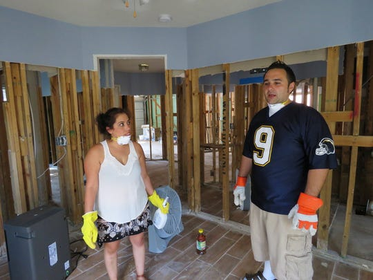 In this Sept. 22, 2017 photo, Marcela and Eli Magana discuss cleaning up their suburban Houston home, which was flooded during Harvey's torrential rainfall. The couple's home in Fort Bend County was flooded when the levels of a nearby reservoir swelled beyond capacity during Harvey and spilled over into neighboring subdivisions. The Maganas and other flooded homeowners in subdivisions near the reservoir are questioning whether officials in Fort Bend County did enough to warn them the reservoir could overflow during a heavy storm event and inundate their homes. (AP Photo/Juan Lozano)