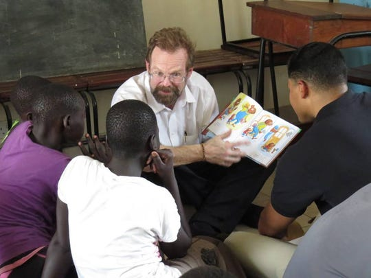 "Christopher Merrill reads from ""The Berenstain Bears"" in Jiba, South Sudan in 2013. Photo from the International Writing Program."