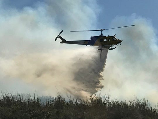 A helicopter drops water Saturday on the fire in the