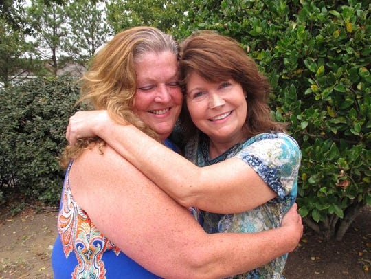 Shana Muse, left, hugs her sister, Suzanne Cooper,