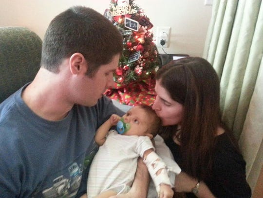 Keith and Kristin Metchis hold their daughter Emily.