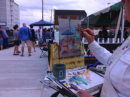 Debra Howard paints a scene at a 2017 Fourth Saturday