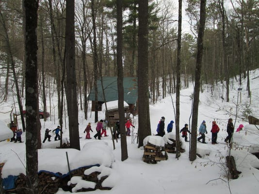 636547439916731259-snowshoers-in-front-of-North-End-Cabin.jpg