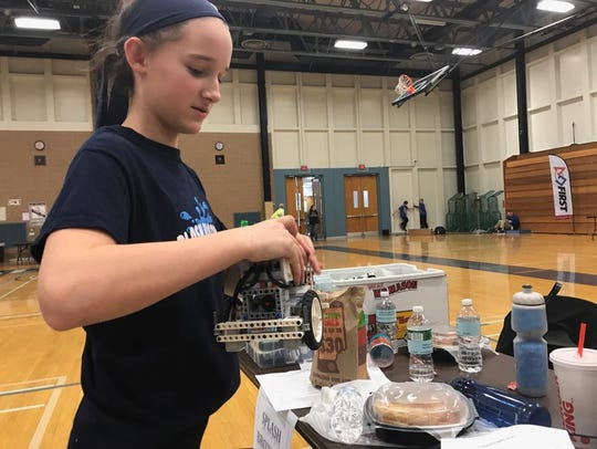Jillian Hagle, 13, takes her team's Lego robot back