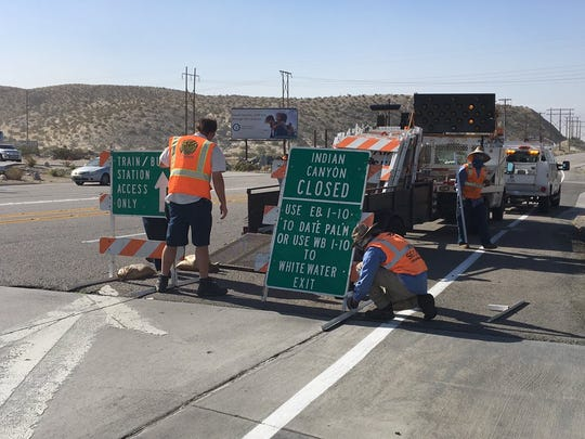 Workers put up signs as they close Indian Canyon Drive