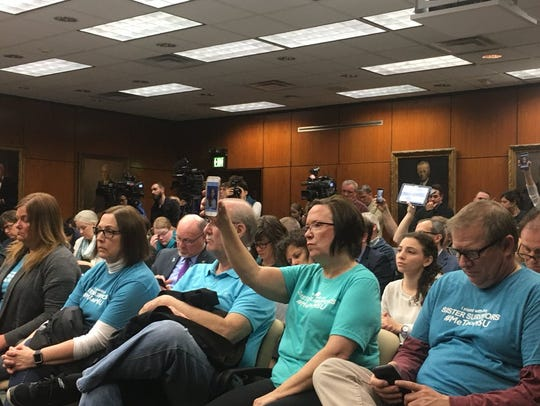 Parents of Larry Nassar victims hold up phones and