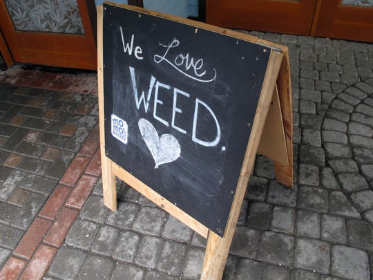 "In this Feb. 27, 2018, photo, a sign reading, ""We Love Weed"" stands outside a state-licensed marijuana shop in downtown Juneau,"