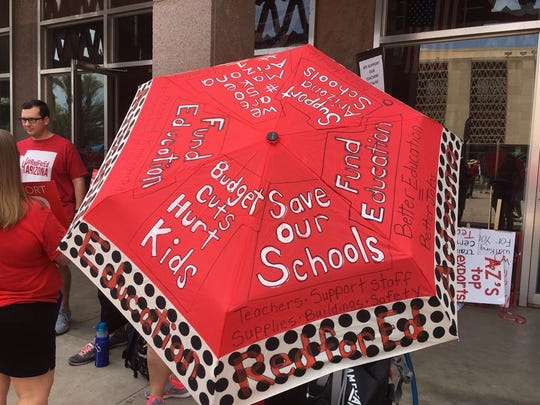 "Reporter Anne Ryman writes, ""Art teacher Lisa Jacobs-Hunter came up with a creative solution to keeping herself cool and still get her message across outside the Arizona Capitol for the #RedForEd washout. She painted an umbrella with the words, 'Save our schools' and 'Budget cuts hurt kids.' """