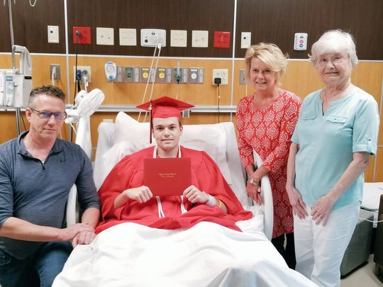 Austin Ely, surrounded by family, graduates from Ozark High School.