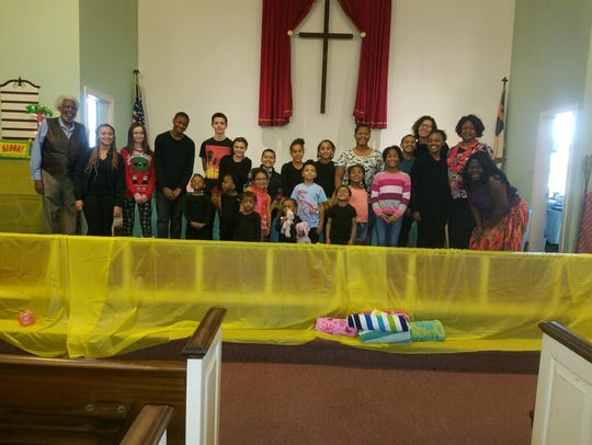 Allie Harper Jr. poses for a photo with children in his congregation at John Wesley A.M.E Zion Church in Chambersburg. Harper was the pastor of the church for 10 years until his passing on Tuesday, April 24.