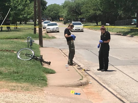 Forensics team members of the Abilene Police Department mark evidence at a shooting on South Third Street just west of Mockingbird Lane on June 1, 2018.