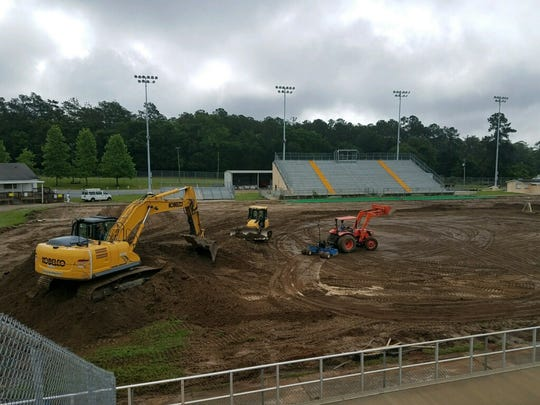 Crews install a new synthetic field at Gene Cox Stadium.