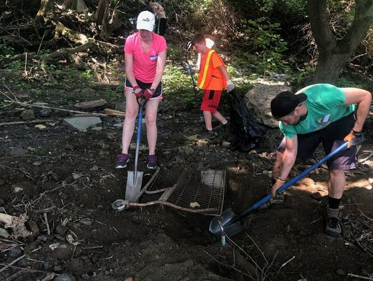 Ohio River Sweep volunteers dig out a shopping cart