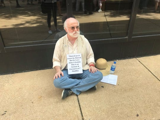 "John Terlazzo, of York County, sits cross-legged on the ground at Continental Square. He was just one of about 100 participants joining the ""Families Belong Together"" protest in York."