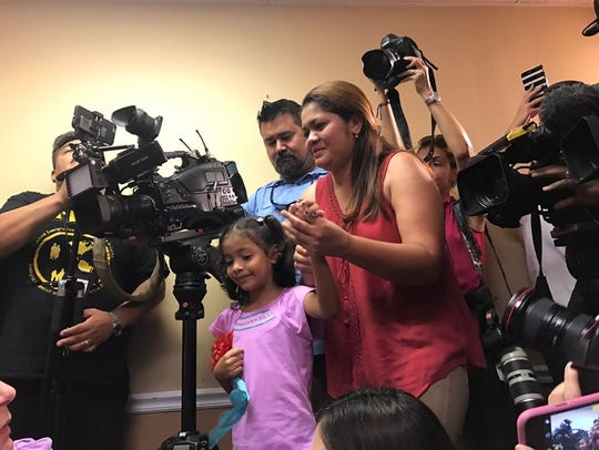 Alisson Ximena Valencia Madrid, 6, holds her mother