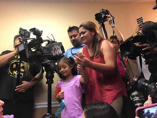 "Alisson Ximena Valencia Madrid, 6, holds her mother Cindy Alinette Madrid-Henriquez's hand before a news conference on Friday, July 13, 2018 in Houston. The pair, who fled from gang violence in El Salvador, were separated for more than a month under the Trump administration's ""zero tolerance"" policy."