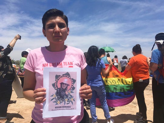 Gabriela Hernandez, executive director of the nonprofit New Mexico Dream Team, holds up an image in Albuquerque, N.M, of a Honduran transgender woman who died while in U.S. custody.