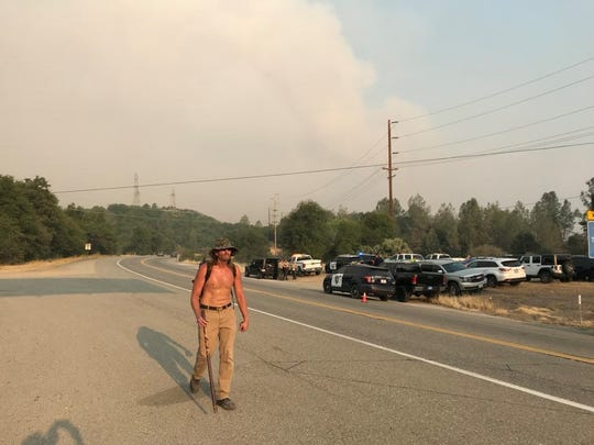Naamon Fox, 53, walks along Highway 299. Fox's home in Shasta was destroyed by the Carr Fire around 5:30 a.m. on Thursday, July 26, 2018.