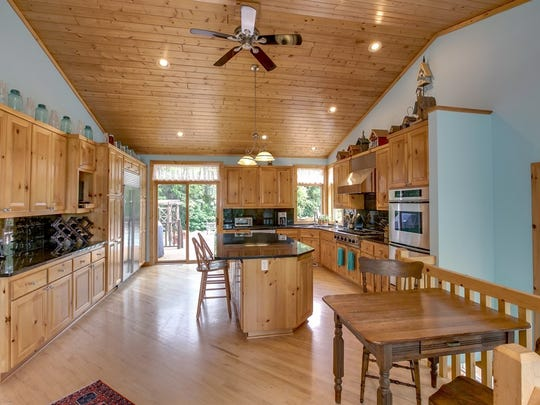 The kitchen has an abundance of cabinets and counter space, stainless steel appliances and a six burner gas Viking cooktop.