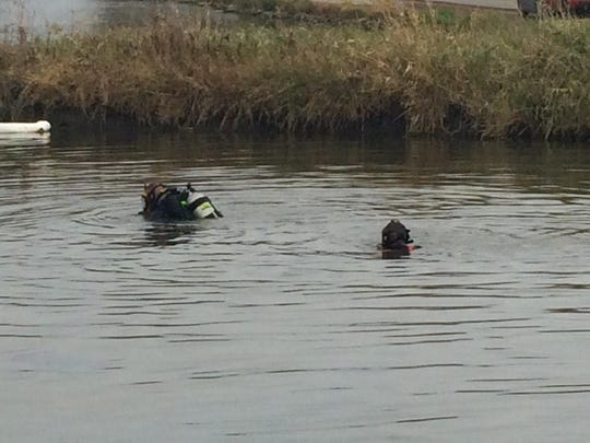 Two divers work in a pond after four people were rescued from the top of a car Friday.