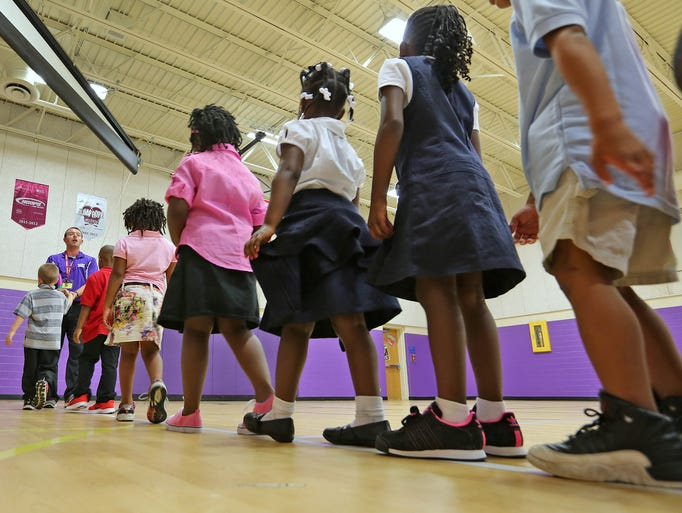 Oliver Helfrich leads his class around the gym during PE on the first day of school, at Eastridge Elementary School, Monday, July 28, 2014.  Warren Township Schools started back to school today.