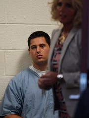 Brandon Vandenburg waits in the hall outside the courtroom
