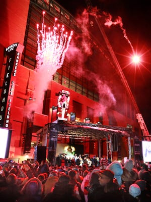 The glow of fireworks paints the scene red during the stroke of midnight at the Downtown Indy New Year's Eve celebration where an IndyCar was lowered over the main stage at Georgia and Pennsylvania Streets.