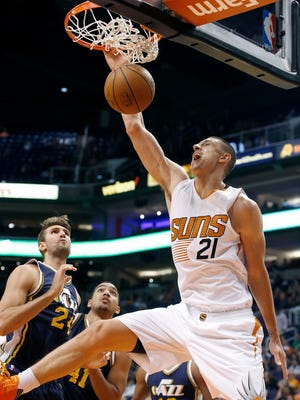 Phoenix Suns' Alex Len (21), of Ukraine, dunks as Utah Jazz's Jeff Withey, left, and Trey Lyles (41) watch during the first half of an NBA preseason basketball game Friday, Oct. 9, 2015, in Phoenix.