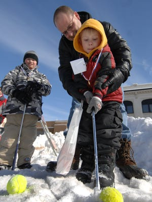 In this 2008 file photo, Jake Harry, center, of Wausau helps his son Tommy, with a putt Saturday afternoon during the annual Ice Tee Golf Classic. The event helps raise money for The Neighbor's Place as spectators use a yellow tennis ball in place of a golf ball and they use brooms, umbrellas and hockey sticks in place of golf clubs.