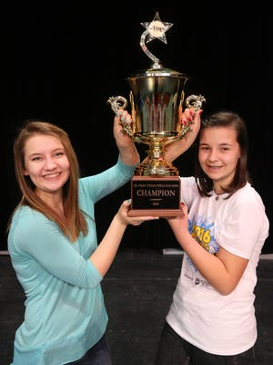 Kate Spitzer, right, gets help from her older sister, Abigail Spitzer, with her championship trophy Friday after winning the 2016 El Paso Times Spelling Bee. The Spitzer family has a history with the spelling bee: Abigail Spitzer won the spelling bee three times.