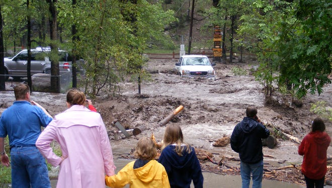 Onlookers watch a car stranded in the flood water of the Rio Ruidoso in 2008.