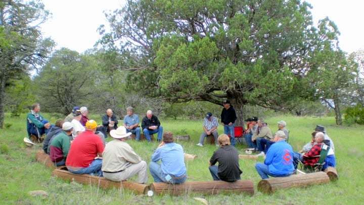 Men gather under the prayer tree at the Ranchman's