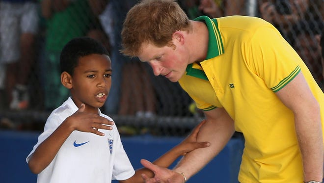 Prince Harry plays football as he visits the ACER Charity for disadvantaged children on June 25, 2014 in Sao Paulo Brazil.