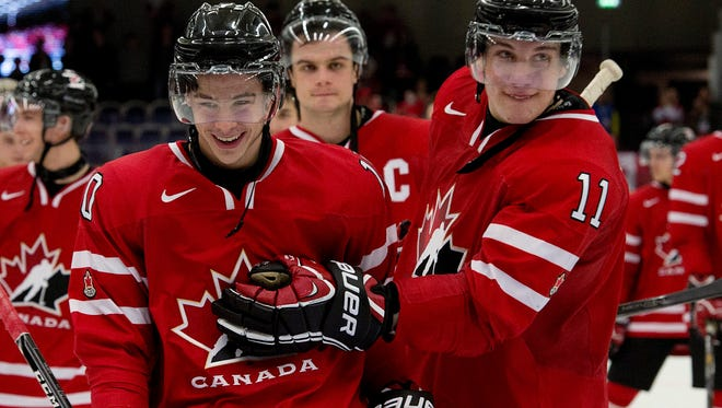 Canada's Charles Hudon (10) and Bo Horvat (11) celebrate as they skate off the ice after defeating the USA 3-2.