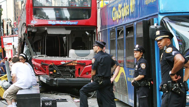 People and police officers stand at the scene of an accident between two double-decker buses at Duffy Square in Times Square on August 5, 2014 in New York City. At least 13 people were injured when the buses collided at 47th Street and Seventh Avenue.