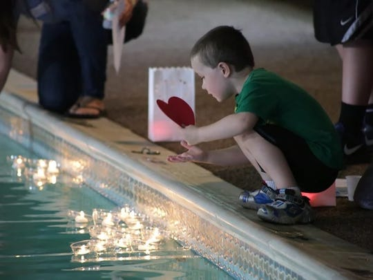 A youngster by the camp pool during a memorial service.